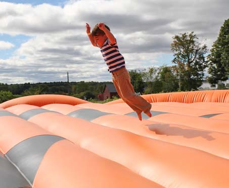 Young Kid Jumping on Inflatable Pillow